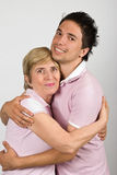 Portrait of mother and son hugging. Portrait of mother and adult son hugging and smiling together and wearing pink tshirts,they are really family,over gray royalty free stock image