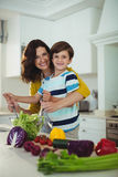 Portrait of mother and son mixing the salad in kitchen. At home Royalty Free Stock Photos