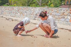 Portrait of mother and son playing with sand by the sea. stock photography