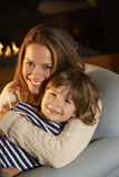 Portrait mother and son sitting in front of fire Royalty Free Stock Photo