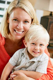 Portrait Of Mother And Son Sitting On Sofa At Home Royalty Free Stock Images