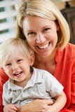 Portrait Of Mother And Son Sitting On Sofa At Home Stock Image