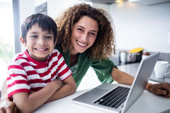 Portrait of mother and son using laptop in kitchen. At home stock image