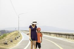 Portrait of a mother and son walking on the street Background mountains and water at Krasiew dam ,Supanburi Thailand stock images