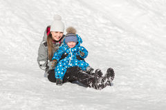 Portrait of mother with son on a winter day, family sits in snow and laughing. Portrait of mother with her son on a winter day, the family sits in the snow and Royalty Free Stock Images