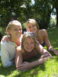 Portrait of mother and teenage daughters laying in grass stock photography