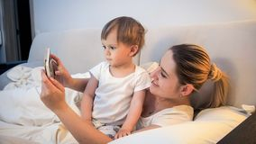 Portrait of young mother toddler son holding digital tablet in bed at night. Portrait of mother toddler son holding digital tablet in bed at night royalty free stock image