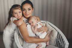 Portrait of a mother with two children at home Stock Photos