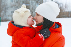 Portrait of mother and 2 years son in similar clothes look at to. Gether in winter stock photos