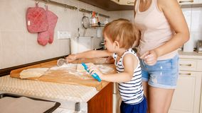 Portrait of mother with 3 years toddler son baking cookies on kitchen at morning. Family baking and cooking at home. Portrait of mother with 3 years toddler son stock images