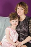 Portrait of a mother and young daughter in a purple room. The daughter is holding my mothers hand royalty free stock photo