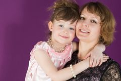 Portrait of a mother and young daughter in a purple room. The daughter hugging mother royalty free stock images