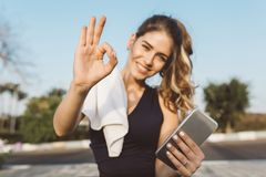 Portrait motivated excited happy young woman in sportswear smiling, expressing positivity to camera in sunny morning. Outside. Fashionable sportswoman, training royalty free stock image