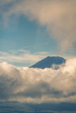 Portrait of mount Fuji summit peeking through clouds. Royalty Free Stock Images