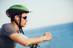 Mountain biker with helmet and sunglasses listening to music and smiling stock photography