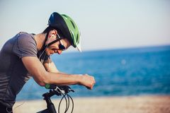 Mountain biker with helmet and sunglasses listening to music and smiling royalty free stock photo