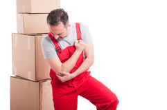 Portrait of mover guy holding his elbow like being hurt Royalty Free Stock Image