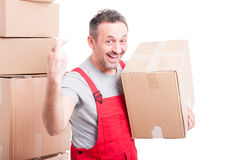 Portrait of mover smiling man holding box showing fingers crosse Stock Photos