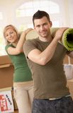 Portrait of moving couple. Portrait of smiling couple moving place, carrying carpet on shoulder together royalty free stock photography