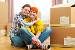 Portrait of moving to new house couple among boxes. Portrait of moving to new house young couple among boxes royalty free stock photography