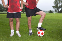 Portrait of muddy soccer players holding ball on field Royalty Free Stock Photography