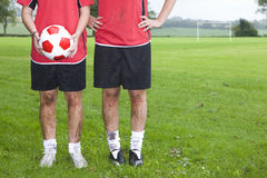 Portrait of muddy soccer players holding ball on field Royalty Free Stock Photo