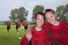 Portrait of muddy teenage soccer teammates hugging and smiling Stock Photo