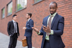 Portrait of multi ethnic  business team. Portrait of multi ethnic business team. Three happy smiling men standing against the backdrop of the city. The African Stock Photo