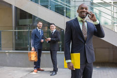 Portrait of multi ethnic  business team. Portrait of multi ethnic business team. Three happy smiling men standing against the backdrop of the city.  The Royalty Free Stock Images