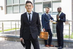 Portrait of multi ethnic  business team. Portrait of multi ethnic business team. Three happy smiling men standing against the backdrop of the city.  The Royalty Free Stock Photos