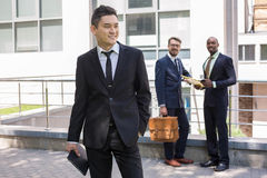 Portrait of multi ethnic  business team. Portrait of multi ethnic business team. Three happy smiling men standing against the backdrop of the city.  The Stock Image