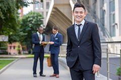 Portrait of multi ethnic  business team. Portrait of multi ethnic business team. Three happy smiling men standing against the backdrop of the city.  The Royalty Free Stock Photo