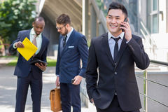 Portrait of multi ethnic  business team. Portrait of multi ethnic business team. Three happy smiling men standing against the backdrop of the city.  The Royalty Free Stock Photography