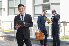 Portrait of multi ethnic  business team. Portrait of multi ethnic business team. Three happy smiling men standing against the backdrop of the city.  The Stock Photography