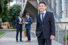 Portrait of multi ethnic  business team. Portrait of multi ethnic business team. Three happy smiling men standing against the backdrop of the city.  The Royalty Free Stock Image