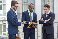 Portrait of multi ethnic business team. Three smiling men standing against the background of city. The one men is European, other is Chinese and African Stock Photography