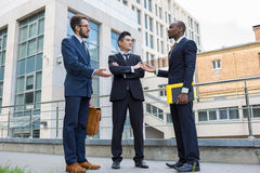 Portrait of multi ethnic business team. Three smiling men standing against the background of city. The one men is European, other is Chinese and African Stock Image