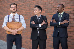 Portrait of multi ethnic business team. Three smiling men standing against the background of red brick wall. The one men is European, other is Chinese and Royalty Free Stock Images
