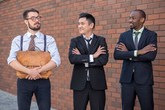 Portrait of multi ethnic business team. Three smiling men standing against the background of red brick wall. The one men is European, other is Chinese and Royalty Free Stock Photos