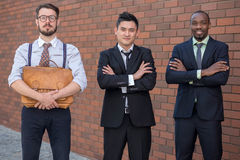 Portrait of multi ethnic business team. Three smiling men standing against the background of red brick wall. The one men is European, other is Chinese and Royalty Free Stock Photography