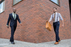 Portrait of multi ethnic business team. Two happy smiling men  walking against the backdrop of the city. The one men is African-American, other is European Royalty Free Stock Image
