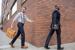 Portrait of multi ethnic business team. Two happy smiling men  walking against the backdrop of the city. The one men is African-American, other is European Stock Photo