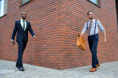 Portrait of multi ethnic business team. Two happy smiling men  walking towards each other against the backdrop of the city. The one men is African-American Royalty Free Stock Photos