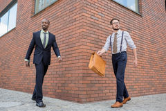 Portrait of multi ethnic business team. Two happy smiling men  walking towards each other against the backdrop of the city. The one men is African-American Royalty Free Stock Images