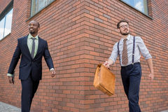Portrait of multi ethnic business team. Two happy smiling men  walking towards each other against the backdrop of the city. The one men is African-American Stock Photography