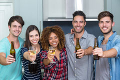 Portrait of multi-ethnic friends showing beer and wine. While standing in kitchen at home Stock Photo