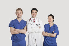 Portrait of multi ethnic healthcare professionals standing with arms crossed over gray background Stock Photo