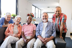 Portrait of multi-ethnic senior people sitting on couch. At nursing home royalty free stock image