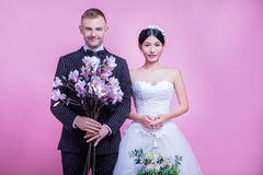 Portrait of multi-ethnic wedding couple holding flowers while standing against pink background Royalty Free Stock Photography
