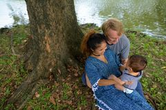 Multi-ethnic young family bonding together at the park stock image
